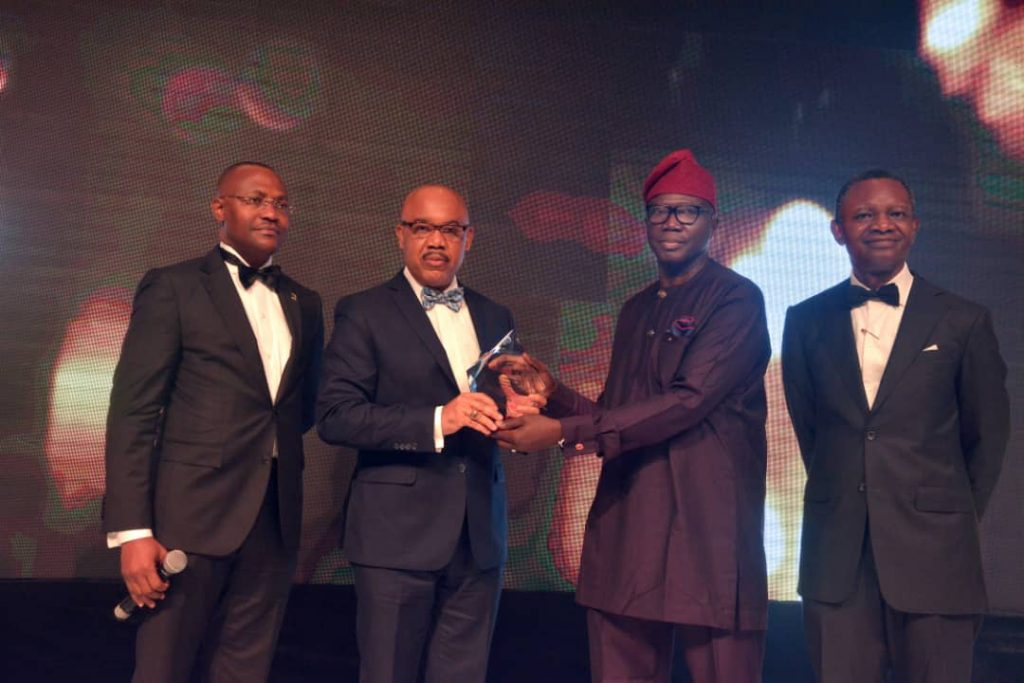 L-R: Oyewale Ariyibi, Chief Financial Officer, FBN Holdings Plc, UK. Eke, Group Managing Director, FBN Holdings Plc receiving the award from Henry Olayemi, Chairman Reward Investments & Services Limited and Frank Aigbogun, Publisher, BusinessDay.